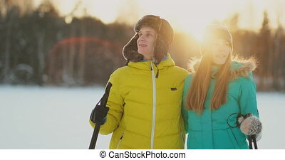 In the winter forest at sunset a man and a woman ski and...