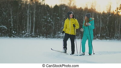 In the winter forest at sunset loving couple skiing and look...