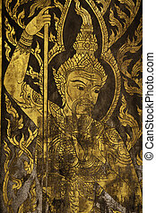 In this picture the wooden door is painted in gold color to shows the high spirit angels in the Thai beliefs. The angels are always at the doors of Ubosot buidlings to protect and salute Lord Buddha.