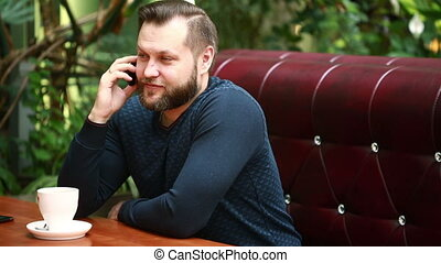 Handsome bearded businessman talking on the phone cheerfully during his coffee break on the cafe terrace