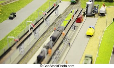 in toy fuel station train pushes tank wagon on rail among roads with small gas-tank truck and people