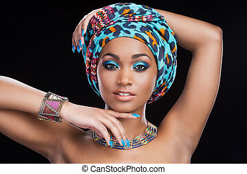 In traditional African style. Beautiful African woman in headscarf and jewelry posing against black background and looking at camera