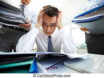 In trouble - Perplexed accountant touching his head being...