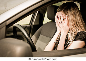 In troubles - unhappy woman in car - Young woman with hands...