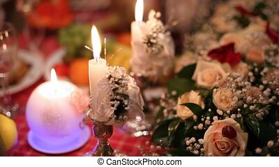 In twilight on festive table there are candles, bouquets, glasses