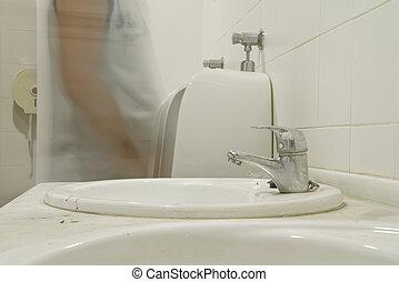 in urinary - a man using a public urinal