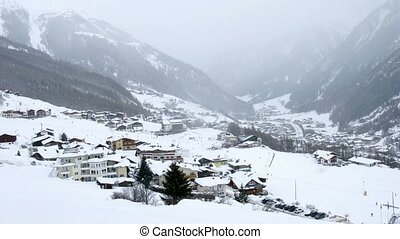 In valley where there are hotels and skiers it is snowing,...