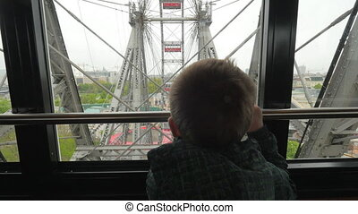 In Vienna, Austria from the window booths of the ferris wheel little boy looks at the city