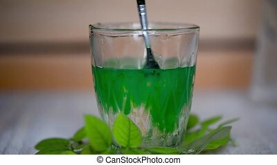 In water in a transparent glass with a brush to mix green...