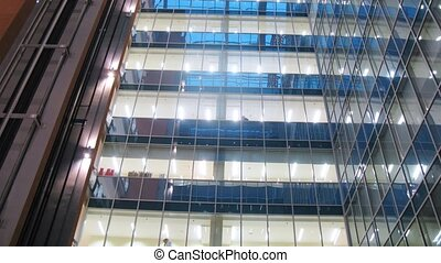 In windows of business center is shone light on stages indoors