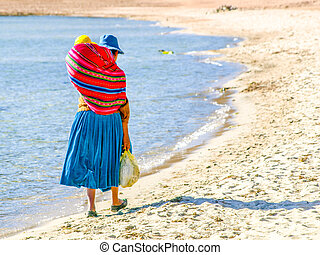 Incan woman with baby in the colorful scarf on a back. Walks on the beach of Island of the Sun at Titicaca Lake, Bolivia, South America.