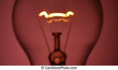 Incandescent filament glows dimmer - Incandescent filament...
