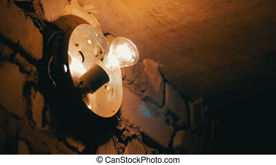 Incandescent Lamp Lights Up on a Stone Wall. Large Bulb with...