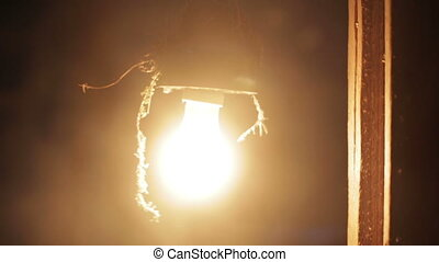 incandescent light bulb - Old light bulb shines and sways in...