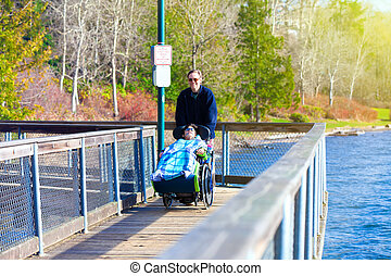incapacitado, menino, em, cadeira rodas, andar, em, parque, com, pai