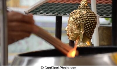 incense and buddha statue - small square of gold leaves...