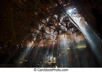 Incense and crepuscular rays in Hong Kong Man mo temple....