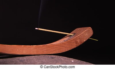 Incense Burning - Burning stick of incense in a wooden...
