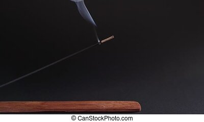 Incense burns on a beautiful wooden stand, on a black background. Aromatherapy for health and prosperity. The concept of meditation, zen and self-knowledge 4k
