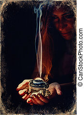 incense in a woman hand, incense smoke on a black background...