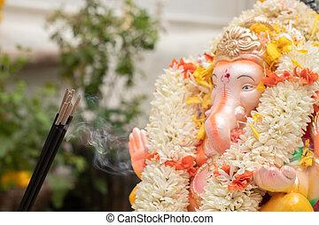 Incense or agarbatti sticks in front of lord vinayaka or Ganesha while worshiping during ganesha chaturthi or vinayaka festival ceremony
