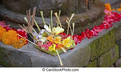 Incense smoke drifts in a gentle breeze over a floral offering placed on an ancient, stone altar in Bali, Indonesia. Video 4k