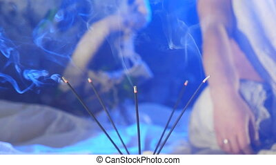 Incense smoke from soothing sticks on a blue background....