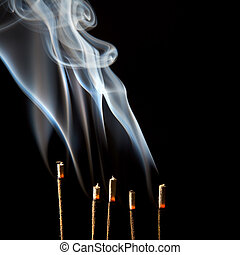 Incense burning with beautiful smoke fumes and wisps