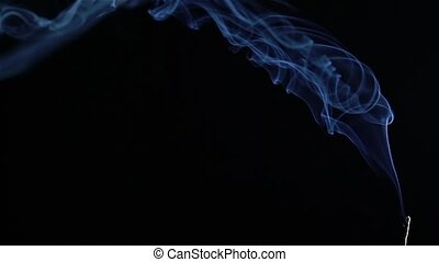 Incense stick on black background. Slow motion.