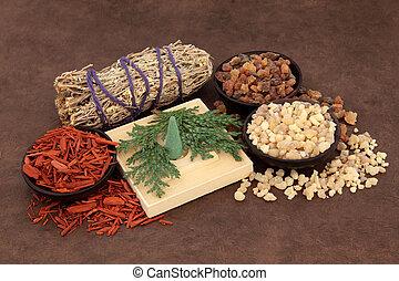 Frankincense, myrrh, sandalwood, incense cones , cedar leaf and smudge stick over lokta paper background.