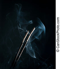 incense with smoke on black background