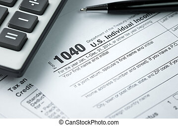 Income tax - Filling income tax form with pen and calculator