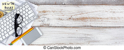 Income tax forms with new changes plus traditional and cyber currency on white rustic desk