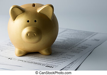 Income tax - Golden piggy bank sitting on income tax form