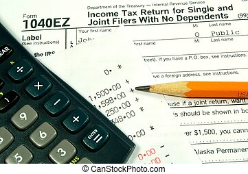 A income tax form with a calculator and pencil