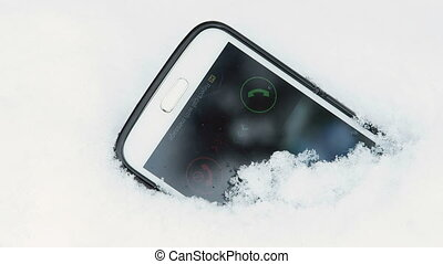 Incoming call on display of lost smart phone in snow