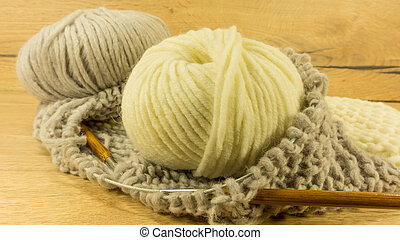 Incomplete knitting project with a woolen ball and wooden needles