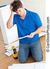 Incomprehensive young man reading the instructions to assemble furniture in the kitchen at home