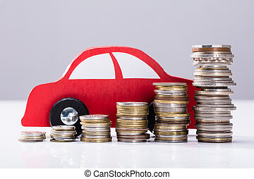 Stacked Coins In Front Of Red Car