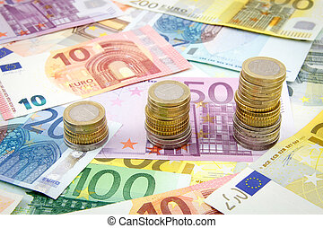 Increasing stacks of euro coins on euro banknotes