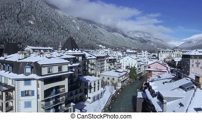 Incredible aerial drone flight in clear blue sky over luxury villa cottage village in snow winter forest Alps mountains