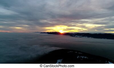 Incredible aerial drone panorama flyover in orange warm evening sunset sky over dense fog cloud mountain hill landscape