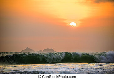 Incredible beautiful orange sunset with mountains in the background and big waves