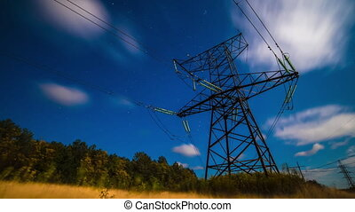 Incredible night sky with stars passing over power line in long exposure timelapse. Beautiful panorama view with clouds and full moon. Nature in the countryside. Astrophotography. 4k.