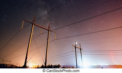 Incredible night sky with stars passing over power line in...