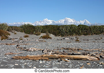 Incredible view of snowy peaks. Mountain landscape including Aoraki Mt. Cook and Mt. Tasman of Southern Alps. New Zealand vista seen from Gillespies Beach.
