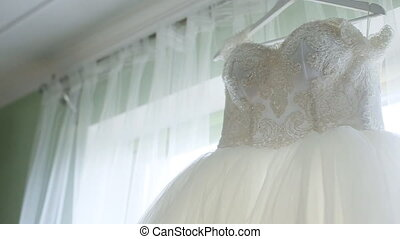 Incredible white wedding dress with a full skirt on a hanger in the room of the bride.