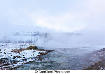 Incredible winter landscape of Iceland. In winter, a source of hot water flows in the mountains