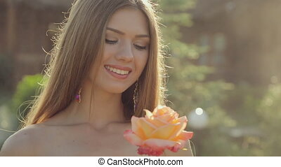 Incredibly beautiful girl with green eyes with long hair dressed in bikini sniffing a beautiful rose in the garden under spray of water