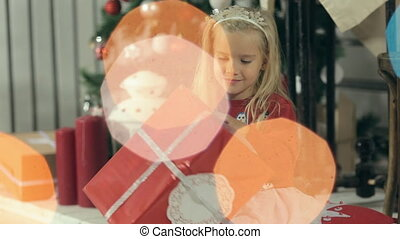 Incredibly beautiful little girl looks at a gift in a red package near the Christmas tree and presents it by her mom